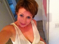 Woman with short dark hair in a white top, taking a selfie from above