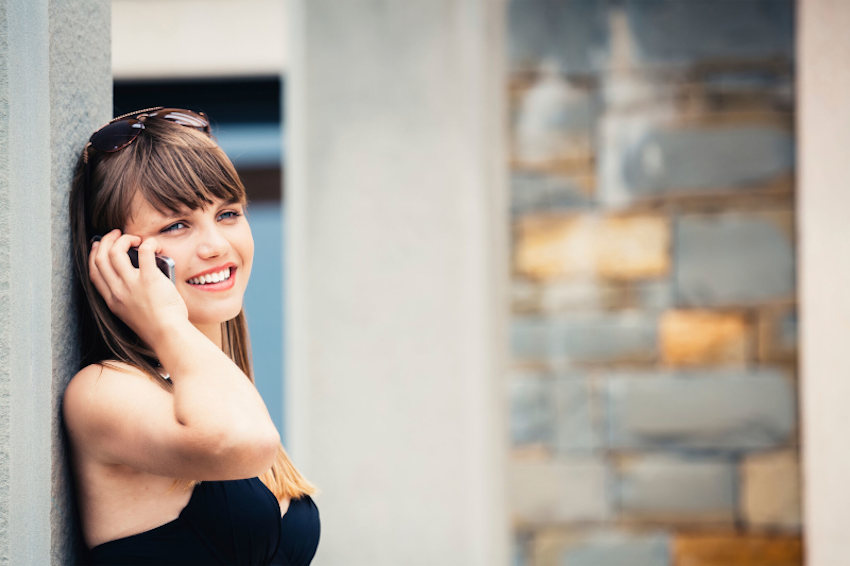 Brunette woman leaning against a wall smiling whilst chatting on the phone